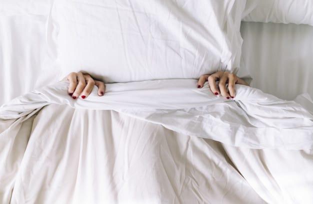 Mulher deitada na cama coberta