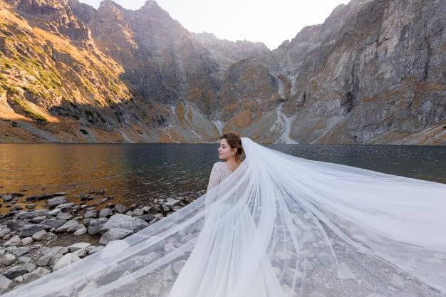 Noiva a beira de um lago cercado por montanhas