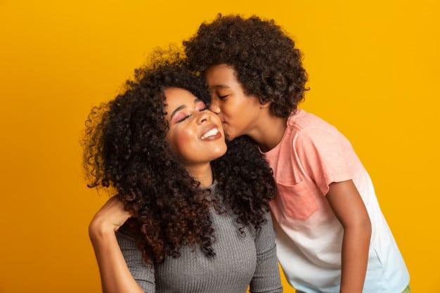 Filho beijando a bochecha da mãe