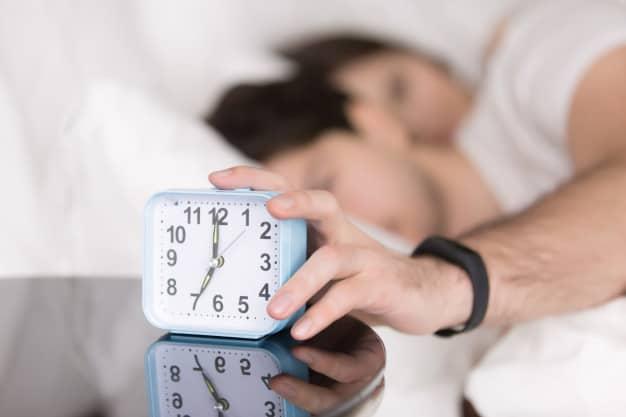 Homem desligando despertador