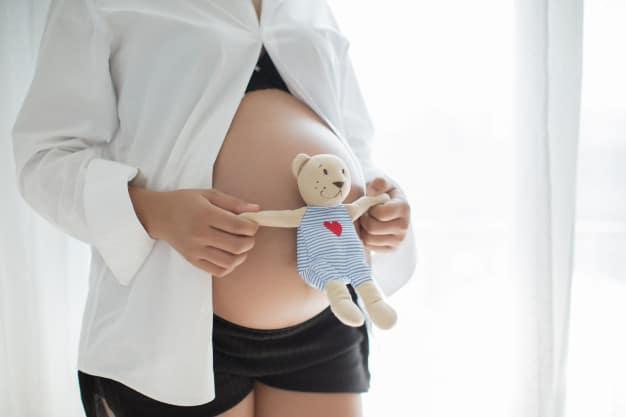 Mulher gravida segurando urso