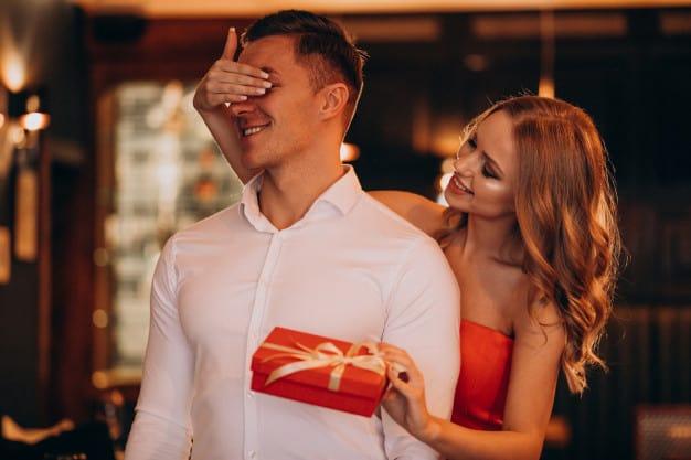 Mulher segurando presente para namorado