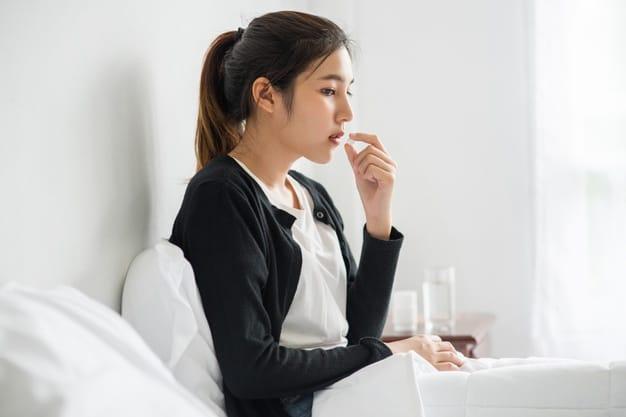 Mulher tomando medicamento