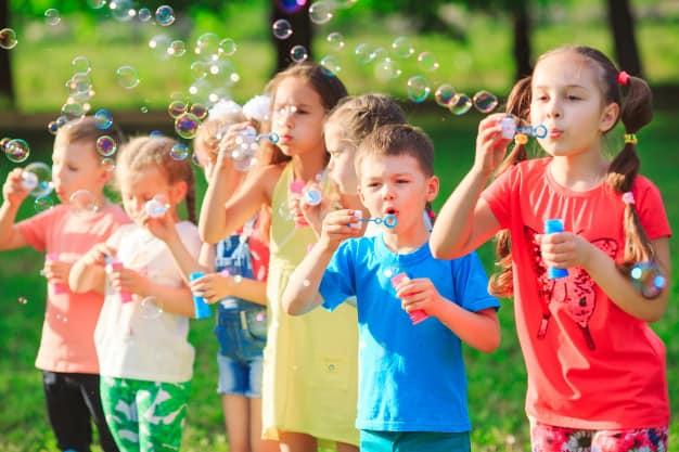 Crianças fazendo bolhas de sabão