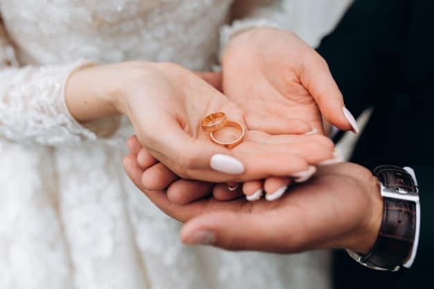 Noivos segurando alianças