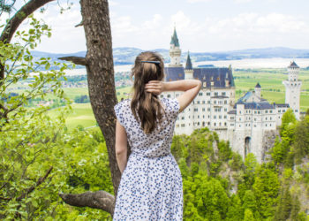 Schwangau, Germany - 05/12/2018: A girl in a long dress looks at Neuschwanstein Castle