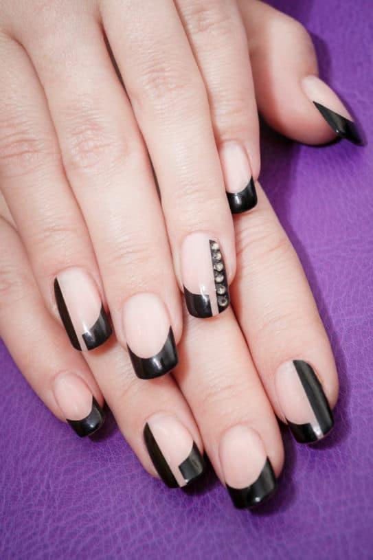 Unhas em tonalidade natural com pequeno detalhe na cor preta.