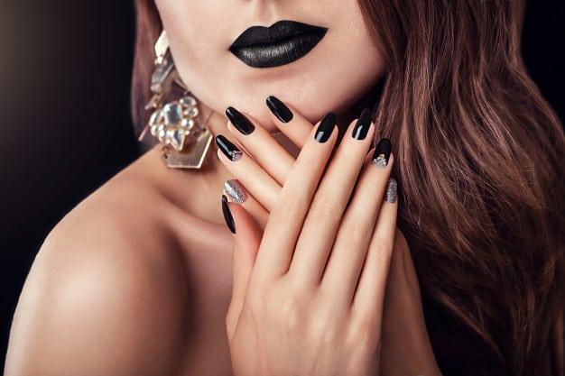 Mulher com unhas decoradas em preto e prata com glitter