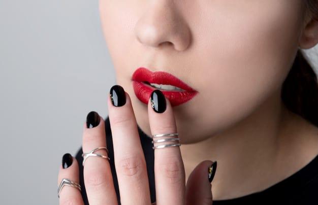 Mulher com unhas pretas decoradas e pequeno detalhe prata no canto da unha