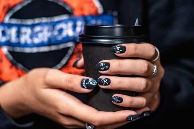 Mulher segurando copo de bebida com unhas pintada de preto com escritas brancas.