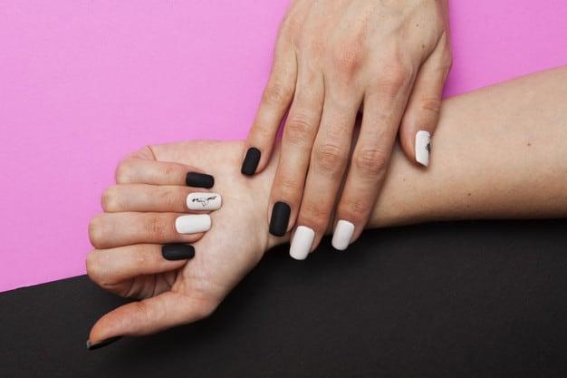 Unhas preta e branca com detalhe de adesivo em uma das unhas.