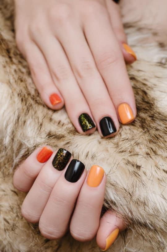 Unhas decoradas em tonalidades laranja e preto, com glitter