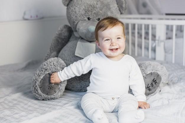 bebê com urso cinza