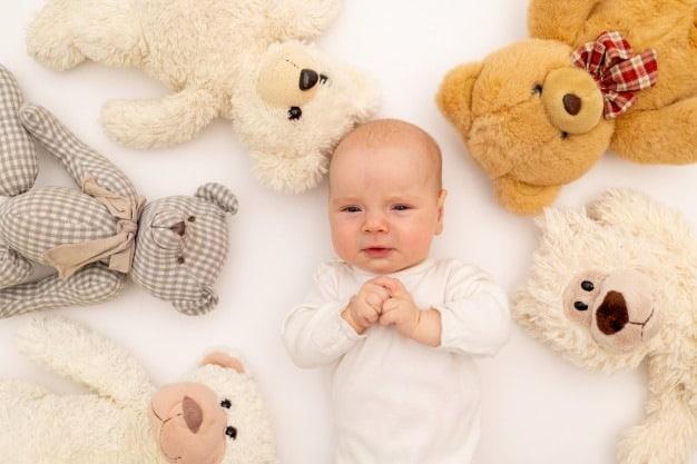 bebê rodeado de ursinhos