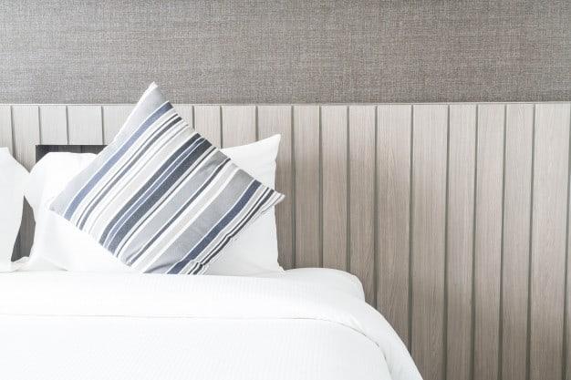 almofada listrada sobre cama posta