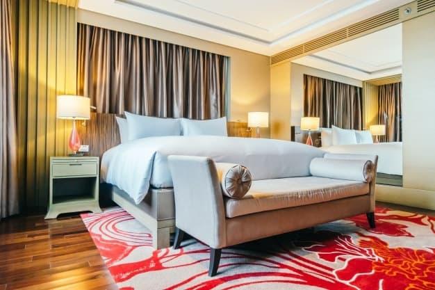 quarto de casal com cama posta e  tapete