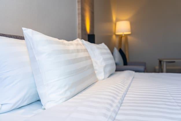 cama posta com travesseiros brancos