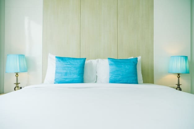 cama posta com almofadas azuis