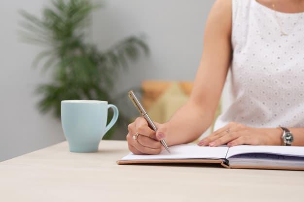 mulher anotando em caderno