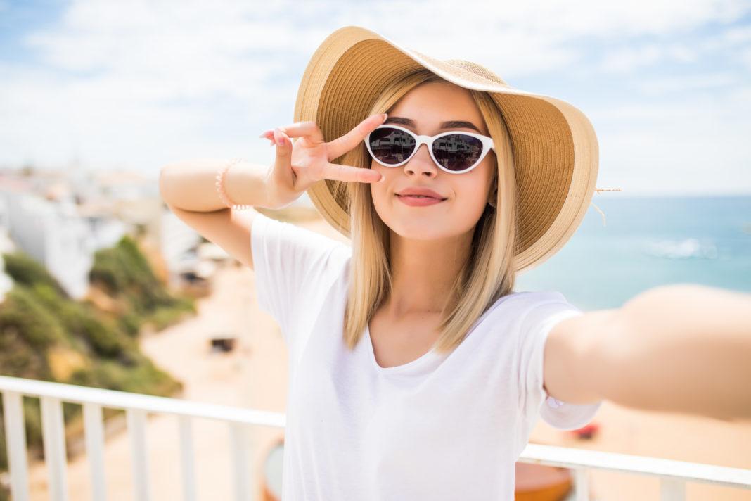 mulher tirando selfie na praia dicas para facilitar sua vida na praia ou piscina
