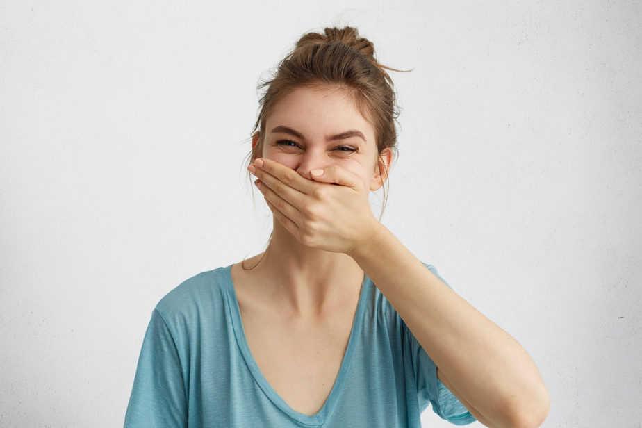 mau hálito mulher cobrindo nariz e boca