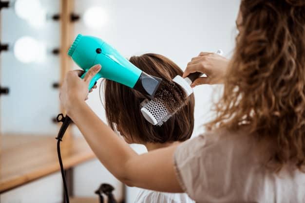 Mulher trabalhando no salão de cabelereiros motivos que levam as mulheres a empreenderem