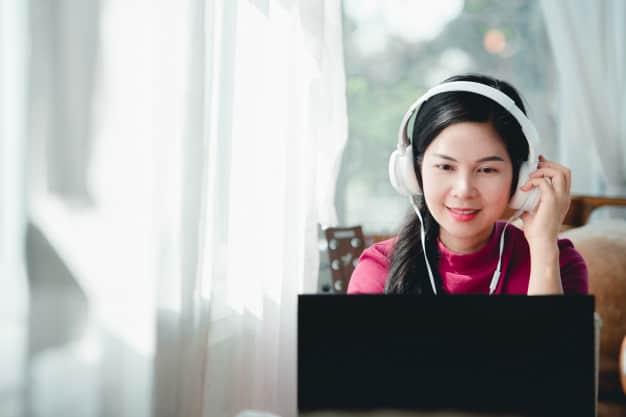 mulher asiática em reunião online com roupa discreta