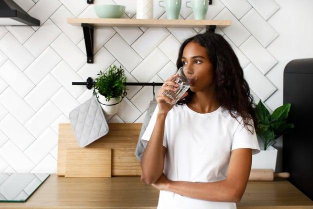 menina dando uma pausa para tomar água produtividade trabalhando em casa