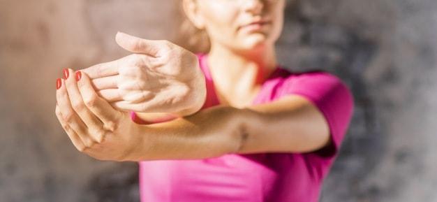 mulher alongando o antebraço exercícios físicos aumentam a produtividade trabalhando em casa
